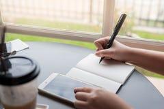 Mão da mulher com escrita da pena no bloco de notas Fotos de Stock