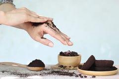 A mão da mulher com esfrega terras de café no fundo de madeira, na beleza e no conceito saudável do cuidado imagem de stock royalty free