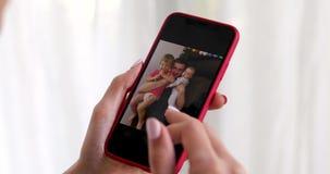Mão da mulher com imagem da família da exibição do smartphone video estoque