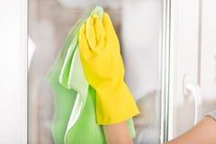 Mão da mulher com a luva protetora amarela e a janela verde da limpeza de pano em casa Imagem de Stock Royalty Free