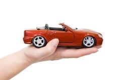 Mão da mulher com o carro de esportes vermelho da terra arrendada foto de stock