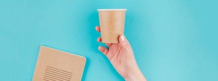 Mão da mulher com o copo de papel e o caderno do ofício imagens de stock