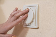 A mão da mulher com o dedo no interruptor da luz imagem de stock royalty free