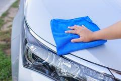 Mão da mulher com o pano azul do microfiber que limpa o carro Imagem de Stock Royalty Free