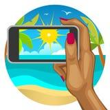 A mão da mulher com o telefone esperto no fundo da praia Foto de Stock