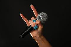 Mão da mulher com os chifres do microfone e do diabo isolados no preto Fotografia de Stock