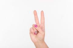 Mão da mulher com os dedos poloneses da mostra dois dos pregos Fundo branco fotografia de stock