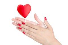 Mão da mulher com os pregos vermelhos que guardam o pirulito do coração Imagem de Stock