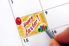 Mão da mulher com a Páscoa feliz do lembrete da escrita da pena no calendário Fotografia de Stock Royalty Free