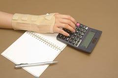 A mão da mulher com a síndrome do canal cárpico que faz cálculos Fotos de Stock Royalty Free