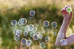 A mão da mulher com sopro de bolhas de sabão coloridas no por do sol Foto de Stock