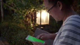 Mão da mulher com a tela verde no telefone esperto no jardim na noite filme
