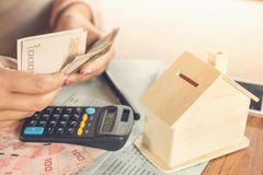 Mão da mulher de negócio que conta a moeda de papel do dinheiro com o livro de conta da economia, o modelo da casa e a calculador Fotografia de Stock