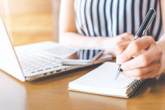 Mão da mulher de negócio que trabalha em um computador e que escreve em um notep Fotos de Stock