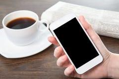 Mão da mulher de negócios que guarda um telefone no escritório imagens de stock royalty free