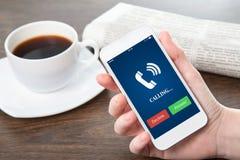 Mão da mulher de negócios que guarda uma tela azul do telefone e o telefone rin imagens de stock