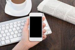 Mão da mulher de negócios que mantém um telefone com contra o fundo o fotos de stock royalty free