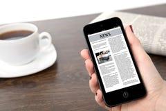 Mão da mulher de negócios que mantem um telefone com notícias de negócios contra o th imagem de stock royalty free