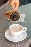 A mão da mulher derrama o chá preto do bule de vidro no copo cerâmico fotografia de stock royalty free
