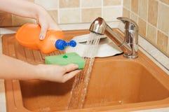 A mão da mulher derrama um líquido da lavagem da louça imagens de stock royalty free