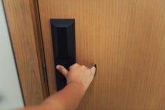 A mão da mulher do close up está guardando o botão de porta a abrir uma porta no hotel , Sistema de segurança e segurança do aces imagens de stock royalty free