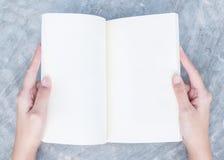 A mão da mulher do close up leu um livro em seu tempo livre na mesa concreta no fundo textured da vista superior sob a luz do dia Fotos de Stock Royalty Free