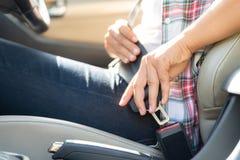 Mão da mulher do close up que senta-se dentro do cinto de segurança da asseguração do carro fotografia de stock royalty free
