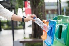 Mão da mulher do retrato do close up que joga a garrafa de água plástica vazia no escaninho de reciclagem imagem de stock