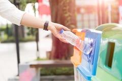 Mão da mulher do retrato do close up que joga a garrafa de água plástica vazia no escaninho de reciclagem imagens de stock royalty free