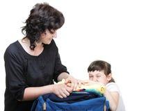 A mão da mulher e da filha comprimiu completamente da roupa e da mala a tiracolo Fotos de Stock Royalty Free