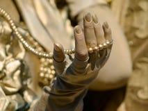 Mão da mulher e grânulos dourados Fotografia de Stock Royalty Free