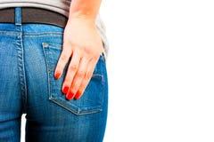 A mão da mulher em suas calças de brim do bolso fotografia de stock royalty free
