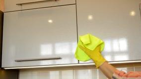A mão da mulher em uma luva de borracha amarela limpa a superfície brilhante de um armário de cozinha plástico moderno com um pan filme