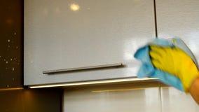 A mão da mulher em uma luva de borracha amarela limpa a superfície de um armário de cozinha plástico moderno com o detergente e u video estoque