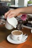 A mão da mulher está derramando o leite no copo de café imagens de stock