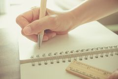A mão da mulher está escrevendo no caderno branco foto de stock