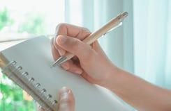A mão da mulher está escrevendo no caderno branco foto de stock royalty free
