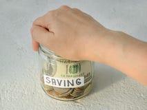 A mão da mulher fecha o frasco de vidro com palavra, moedas e nota de dólar da economia em um fundo branco Conceito do dinheiro d fotos de stock royalty free