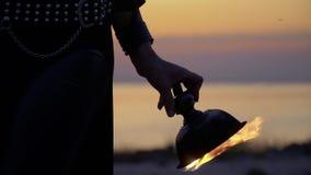 A mão da mulher gerencie a bacia de fogo no fundo do por do sol video estoque
