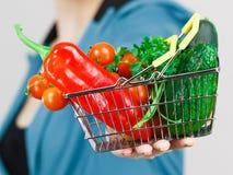 A mão da mulher guarda o cesto de compras com vegetais imagens de stock royalty free