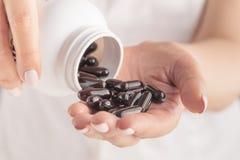 A mão da mulher guarda os comprimidos brancos da medicamentação, derrama de uma garrafa branca na palma imagens de stock