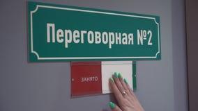 A mão da mulher move a placa para ocupado na porta com sala de reunião do texto do russo video estoque