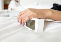 Mão da mulher no despertador digital branco no quarto Fotografia de Stock