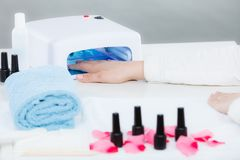 Mão da mulher no tratamento de mãos de secagem conduzido uv do gel da lâmpada imagem de stock