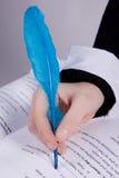 Mão da mulher nova que prende um quill azul Imagem de Stock Royalty Free