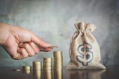 A mão da mulher pôs moedas para empilhar das moedas, um dinheiro de salvamento para o conceito futuro do investimento fotografia de stock royalty free