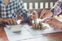 A mão da mulher pôs moedas para empilhar das moedas, um dinheiro de salvamento para o fut fotografia de stock