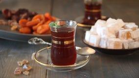 A mão da mulher põe a placa com os doces secos dos frutos sobre a tabela de madeira com chá turco em uns copos de vidro tradicion vídeos de arquivo