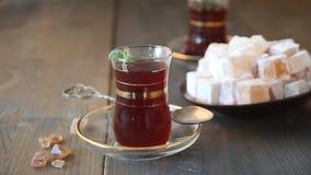 A mão da mulher põe a placa com prazer do lokum sobre a tabela de madeira com chá turco em uns copos de vidro tradicionais orient video estoque