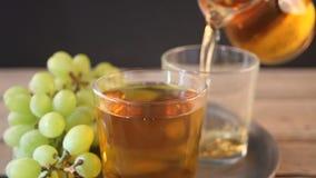 A mão da mulher põe um vidro vazio na bandeja e na bebida de derramamento de uvas verdes filme